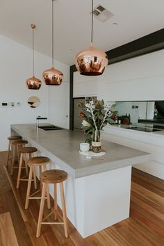 Chifley house in Canberra, Australia designed by Studio Black Interiors. This modern kitchen is contemporary but full of warmth and elegance. The concrete benchtop paired with the warmth of the copper pendants, timber stools and chrome and black sink mixer creates a modern, stylish look. White cabinets