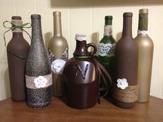 DIY repurposed wine bottles! Centerpieces for rustic wedding or party.  Goo-gone makes labels virtually fall off. Grab some spray paint, hot glue gun, and tons of ribbon.  To write letters or numbers on bottle, write them with puff paint or in hot glue, all it to dry and then spray paint over it!