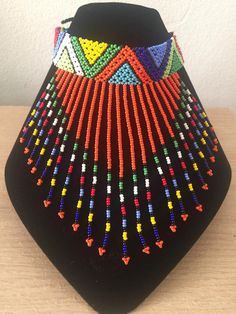 Beaded choker with a rope closure. Choker measures approximately 10 inches. Hand beaded by the young Zulu women from Durban, South Africa. *While all efforts are made to show the jewelry as accurately as possible, dimensions and colors may vary slightly. African Tribal Jewelry, African Beads Necklace, Beaded Choker Necklace, Tribal Necklace, Beaded Jewelry Patterns, Fabric Jewelry, African Accessories, Beaded Purses, Bead Jewellery