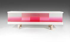 """Andrea BRANZI (Né en 1938) & METEA (Éditeur) Élégant meuble de présentation """"Borealis"""", 2011, piétement quadripode formé de rondins de bouleau, corps parallélépipédique en bois laqué blanc, parements et vantaux coulissants en altuglas teinté dans un dégradé de rose fluo, une étagère médiane. Haut. 76 cm - Larg. 230 cm - Prof. 50 cm A """"Borealis"""" sideboard, 2011, white lacquered wood frame, pink plexiglas sliding doors. A central shelf, birch legs."""