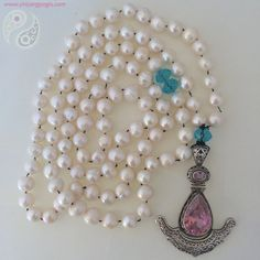 108 freshwater pearls made with mantra and intention enhanced by a sterling silver and pink tourmaline pendant. The guru and accent beads are done in blue topaz.