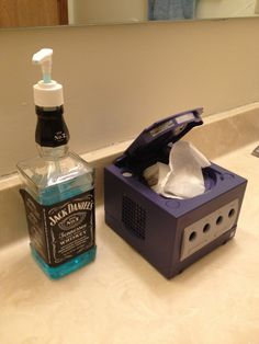 Get rid of the cheesy JD bottle. I want the GameCube Kleenex box. More memes, funny videos and pics on Kleenex Box, Hipster Bathroom, Console Style, Deco Gamer, Man Cave Bathroom, Men's Bathroom Decor, Guys Bathroom, Bathroom Cabinets, Nerd Cave