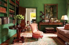 The color palette of jewelry designer Elizabeth Locke's living room is brought together in a red-and-green antique Oushak | archdigest.com