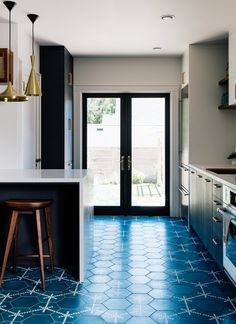 Vintage lover Sarah Benson worked with local firm Bright Designlab to gently update her 1925 home in Portland, Oregon. In the kitchen, Moroccan cement tiles featuring a blue Hex Dot pattern by Popham Designs cover the floor.