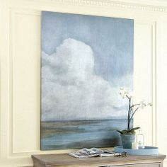 In this calming cloudscape by Jordan Thurston, monumental clouds of soft white rise above an endless plain layered in tones of deep moss green, soothing spa and smoky gray blue. The colors blend easily with our favorite fabrics and wood tones.