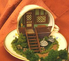 A quarter scale front porch scene in a T cup, part of the Yakminis club project shown at the Spring 2010 Seattle Dollhouse Show.