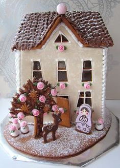 Gingerbread house with tiny pink flowers, a reindeer, and a matryoshka doll cookie.
