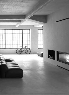 A bike, large windows, a sofa & a fireplace--all that is needed are the people