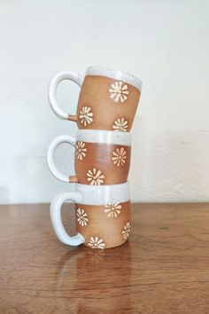 Cheerfully made ceramic mugs with a fun daisy pattern. Each mug is thrown on the wheel and then hand-stamped with a hand-carved daisy stamp.