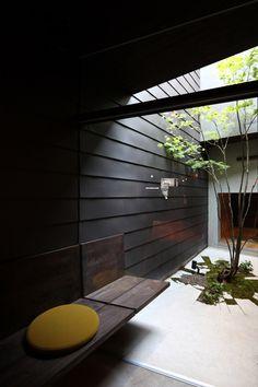 Courtyard with black clapboard siding and cracked floor. Yamaga by Méga. Photo by Nagaishi Hidehiko.
