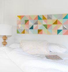 This is an excellent example of something which can be created at home – triangles cut out of colored paper form the headboard of this otherwise simple bedroom