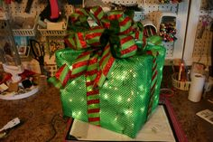 pieces of chicken wire to make her box, added some inexpensive clear Christmas lights, covered the boxes in a nice shiny fabric and topped the box off with a crisp Deco Poly Mesh bow.