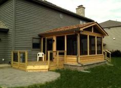 spacious and airy screen porch with a belgard wall around its base and decks on each