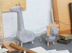 A concrete giraffe and a concrete lion standing on a desk