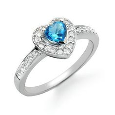 This beautiful white gold ring features a heart shaped blue topaz gemstone in the center accented by diamonds. The blue topaz gemstone is heart shaped and prong set and sits in the middle of round glittering diamonds. The diamonds have H/I color and S Blue Topaz Diamond, Topaz Gemstone, Diamond Heart, Diamond Rings, Gemstone Rings, Wedding Band Sets, Silver Rounds, White Gold Rings, Beautiful Rings