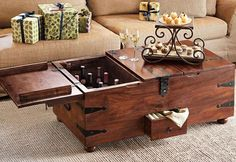 This cool new Wine Bar Treasure Trunk. This beautiful coffee table / bar wine bar styled after old treasure ship and save up to 12 bottles of wine and cocktail accessories. A hidden center compartment, small front drawer to hold the remote and wooden arms that fold out to support the lid open for an extra table space. This hand-made from sustainable, sheesham wood with hand-wrought iron hardware and features three hinge lid for easy access into roomy main compartment, removable divider for wine
