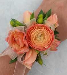 A wrist corsage designed with peach ranuculus, spray roses and green hypericum berries. - Flowers by Candlelight Floral & Gifts, Wayzata MN