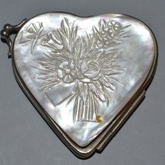 A SMALL MOTHER-OF-PEARL FRONT & BACKED HEART SHAPED PURSE, the front carved with a bouquet of flowers.