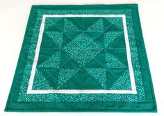 """Dress up a table the easy way with this handmade quilted vivid green tablecloth. Add to the center of a dining table, sofa table, patio table or side table. Add a centerpiece of flowers or candles.  I made this geometric patchwork top with fabrics of green and white print, green swirly patterned print, and white print border. The backing is done with matching green and white print. The hand stitched double binding is the swirly patterned green fabric.  Measures 17"""" x 17"""""""