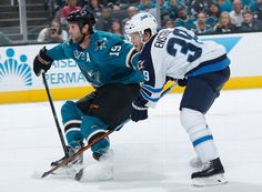 San Jose Sharks forward Joe Thornton battles Toby Enstrom of the Winnipeg Jets for the puck (Oct. 11, 2014)