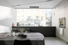 Tämän upean, modernin kaupunkikodin keittiön ikkunasta voi katsella kadun kauniita jugend-taloja. Iso ikkuna tekee keittiöstä ihanan valoisan. Arkkitehdin suunnitelman mukaan toteutetussa keittiössä on tyylikäs ja kestävä komposiittitaso sekä arkkitehdin ja valaistussuunnittelijan luoma upea valokuilu, jossa on ohjelmoitava led-valaistus.