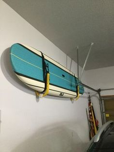 A metal SUP wall rack with suspension straps that holds 1 SUP. Garage Racking, Suspension Straps, Garage Storage Solutions, Wall Racks, Paddle, Boards, Home, Design, Planks