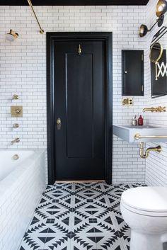 Black and white floor tile, black bathroom door, brass fixtures, bathroom design