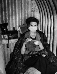 24 Oct 1940, England, UK --- A woman wears a surgical mask to protect others from her cold in a British air raid shelter during World War II ~