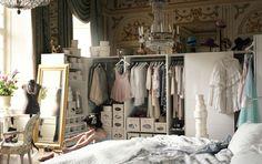 Hvid soveværelsesopbevaring i et luksuriøst rum. Der er en stor, hvid seng i forgrunden