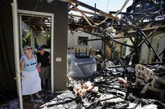 EMBERS: Karoline, left, and Tony Chavez looked at the remains of their living room on Thursday after a fire caused by fireworks gutted their Eugene, Ore. home. (The Register-Guard/Associated Press)