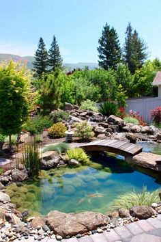 What a relaxing setup for a backyard, complete with flowers, stream of water, a pond with koi fish and your own wooden bridge