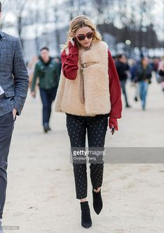 Olivia Palermo wearing a fur vest, red jumper and black pants outside Carven during the Paris Fashion Week Womenswear Fall/Winter 2016/2017 on March 3, 2016 in Paris, France.