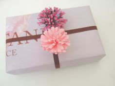 tutorial for cute paper pom poms to add to gifts