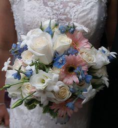 Bride's bouquet contains Vendela white Roses, pink mini Gerbera Daisys, light blue Delphinium, white Lisianthus, Stephanotis and varigated Pittosporum. I designed this.