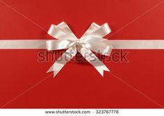 White gift ribbon bow on red wrapping paper background horizontal