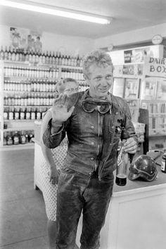 Steve McQueen in motorcycle gear making a pit stop for a soda pop.