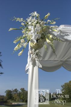 Spray of white flowers on the corner of a wedding tent.