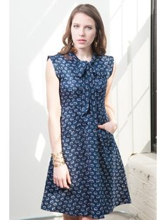 You'll feel cute as a button in this handmade dress, screen-printed with darling little elephants, tumbling on a navy background. The fabric tie at the nec