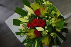 Leucadendron, longiflorum lilies, white spray roses, red roses, white alstroemeria and palm leaves
