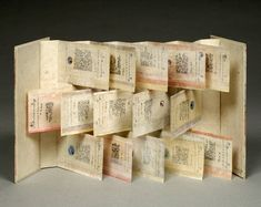 """April Diary by Hedi Kyle, 1979. This is the original work of the form that has become known as the """"Flag Book."""" It is the single most influential structure in the world of contemporary bookmaking. This method of construction, employing tipped on page fragments on alternating sides of a concertina structure, has been adopted by artists worldwide for the creation of unique and multiple bookworks. 26 x 14 x 1 centimeters. Created 1979. Lent by Richard Minsky."""
