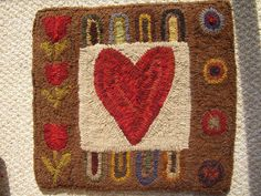 """This is my newest original hooked design. The wool around the heart is showing up white but it's not.It's more of a textured beige or dirty white.Sampler Rug is 14"""" X 15"""" $145 with FREE Shipping. SOLD jstoff@windstream.net"""