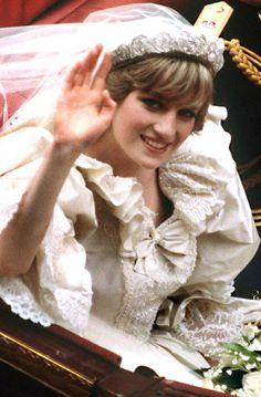 Diana waves as she rides in the carriage to Buckingham Palace immediately after her wedding to Prince Charles.