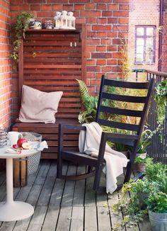 Balcón con mecedora negra y un banco de madera marrón con un panel de pared y estantes.