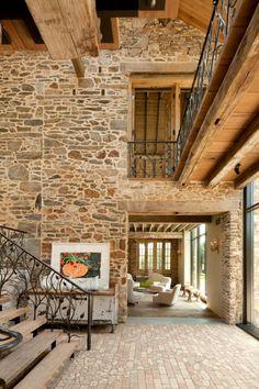 paredes decoradas, casa en estilo rústico de dos plantas, escaleras de madera, techos altos y paredes de piedra