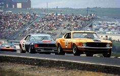 "Mark Donohue in an AMC Javelin chases Parnelli Jones' Mustang. Dan Gurney: ""It was the very best kind of road racing that I can remember. All of the factories were behind us and we had the best drivers in this country competing. We also raced on all the best natural road circuits in North America and unlike today, we had great fans who could really identify with the cars that were on the track. It's too bad that it all had to go away."""