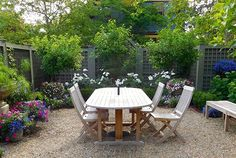 For a city residence in Providence, Rhode Island, New England landscape designer Andrew Grossman anchored a casual dining area with a pea-gravel patio and surrounded it with stately boxwood hedges, hydrangeas, roses, and perennials to achieve the feel of a secret garden.