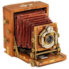 """The 1893 Instantograph, 1893 Lancaster, Birmingham. Small folding plate camera, size 3 1/6 x 4 in., tropical wood with brass fittings, dark-red bellows, lens: """"Beck Symmetrical"""", shutter speeds 1-1/100 sec. (all speeds one time)."""