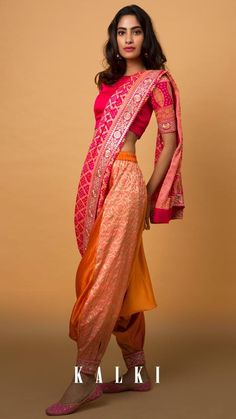Dhoti Sarees? Yes, they're a thing! We mean it. Ready to wear dhoti sarees are the best advancement sarees have had in this decade. They're super easy to carry without compromising on the essence of a traditional saree. This is a must have for all you edgy fashion lovers out there! Latest Indian Saree, Indian Sarees Online, Indian Gowns, Indian Wear, Dhoti Saree, Lehenga, Indian Designer Suits, Saree Photoshoot, Indian Wedding Outfits