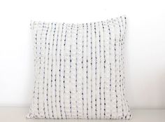 Bring a fresh and summery touch to your home with this unusual pillow. Modern pillow with a textural weave in white cotton, a little like crochet. Incorporated into the weave are delicate stripes in shades of indigo blue. Its a high quality fabric produced for a top Italian fashion house, and is perfect to bring texture and freshness. The back of the pillow is made from upholstery grade heavy natural linen: a naturally textured neutral that compliments the fabric on the front. Linen is by…