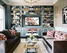 living rooms - charcoal gray velvet modern sofas hot pink ikat silk pillows mirrored coffee table glossy blue stools blue built-in media unit TV buddha blue silk drapes